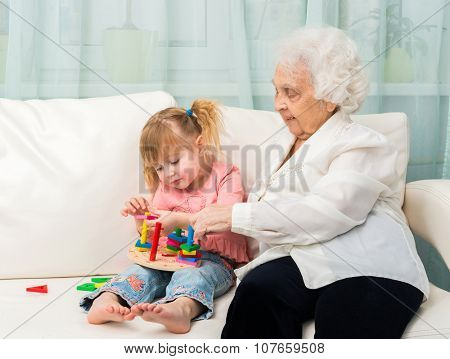 grandmother and granddaugter with cat on white sofa poster