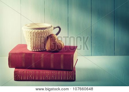 Cup of coffee standing on old books and a heart