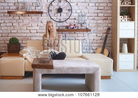 Attractive young blonde woman sitting on sofa at retro home, smiling, looking at camera.