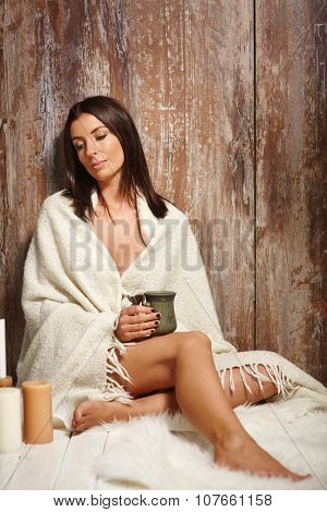 Beautiful sexy woman sitting on floor front of wooden surface, drinking tea, looking away.
