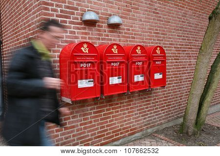 People passing by a brick wall with postboxes.