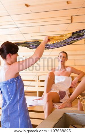 Sauna clerk fanning air to women during infusion