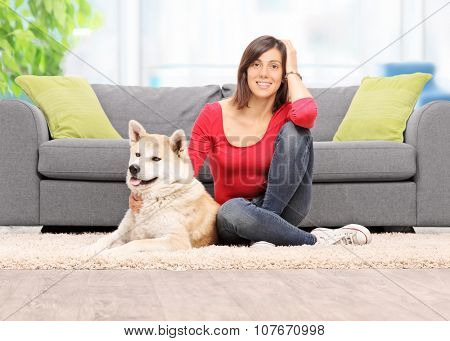 Young woman sitting on the floor with her pet dog in front of a modern sofa at home shot with tilt and shift lens