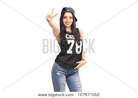Cool girl in hip-hop clothes making a hand sign and looking at the camera isolated on white background