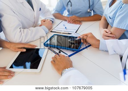 technology, people and medicine concept - group of doctors with tablet pc computers and clipboards meeting at hospital