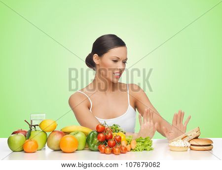 people, junk food, healthy eating, diet and weight loss concept - woman with fruits and vegetables rejecting hamburger over green background