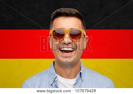 summer, accessories, patriotism, citizenship and people concept - face of smiling middle aged latin man in shirt and sunglasses over german flag background poster