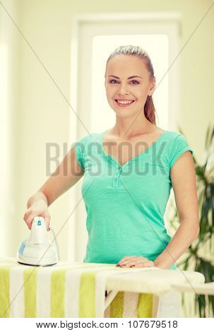 people, housework, laundry and housekeeping concept - happy woman with iron and ironing board at home poster