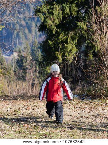 Little Girl Walking In Autumn Forest