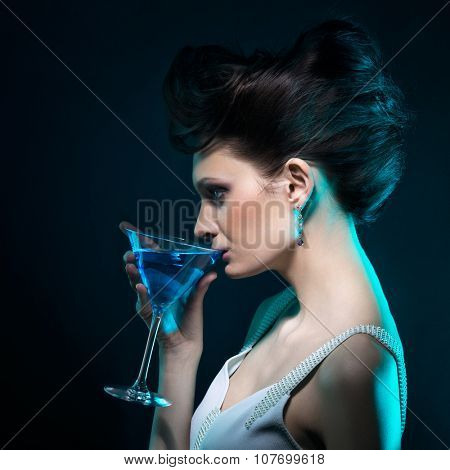 Young woman with martini glass in blue light on dark background