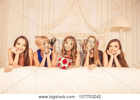Cheerful Girls Celebrating A Bachelorette Party Of Bride Liying On The Bed