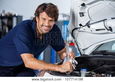 Portrait of happy male mechanic leaning on car with open hood at garage