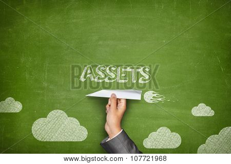 Assets concept on blackboard with paper plane