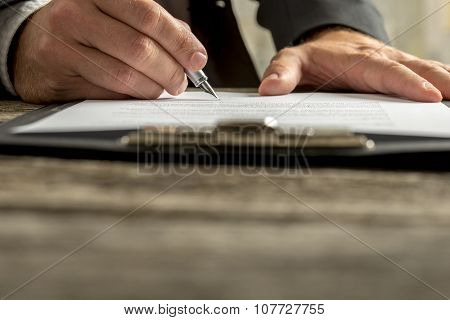 Closeup Of Businessman Signing Contract, Document Or Legal Papers