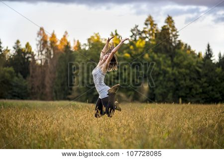 Happy Cheerful Young Woman Jumping In The Air In The Middle Of Golden Meadow
