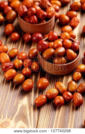 Ripe jujubes on brown wooden table close up poster