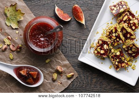 Fig jam jar and a white plate full of fig turkish delight with pistachio nuts on a dark wooden background poster