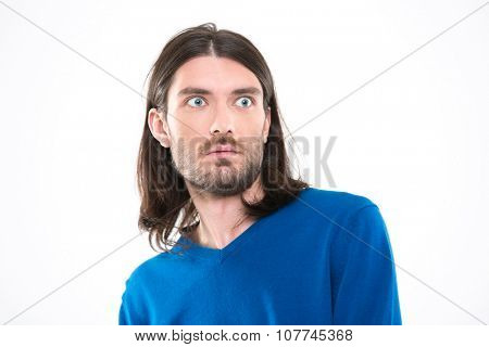 Young handsome man with long hair in blue sweetshirt looking surprised