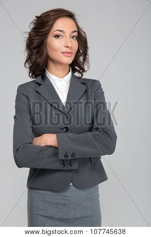 Smug priggish assured successful young curly business woman in gray suit with arms crossed