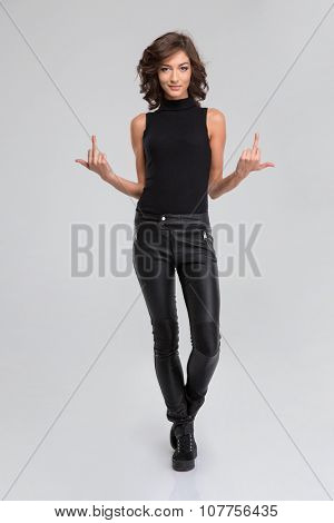 Pretty young curly attractive woman in black leather pants and top showing rude gesture with middle finger