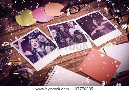 High angle view of office supplies with blank instant photos against happy friends having fun together