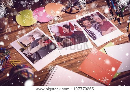 Snowflakes against high angle view of office supplies with blank instant photos