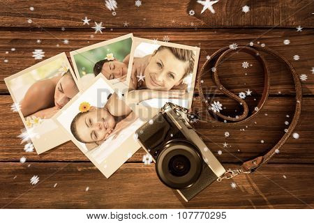 Beautiful woman lying on massage table at spa center against instant photos on wooden floor