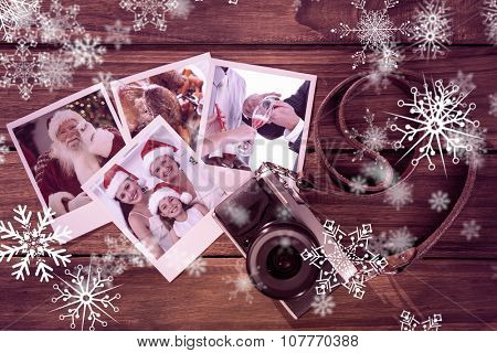 Smiling santa holding his glasses against instant photos on wooden floor