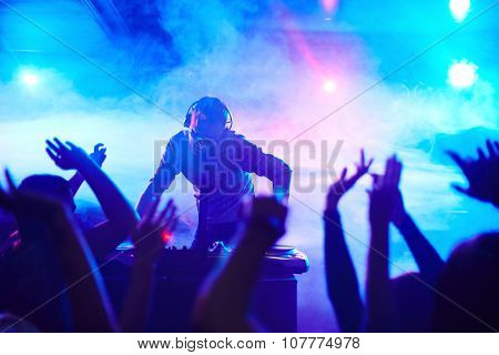 Energetic deejay standing in front of dancing people in club