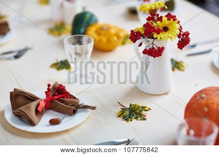 Autumn ashberries, flowers and leaves on traditional Thanksgiving served table