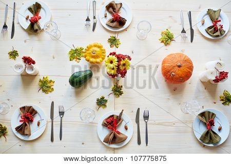 Ripe ashberries, flowers, candles, squashes, glassware and tableware