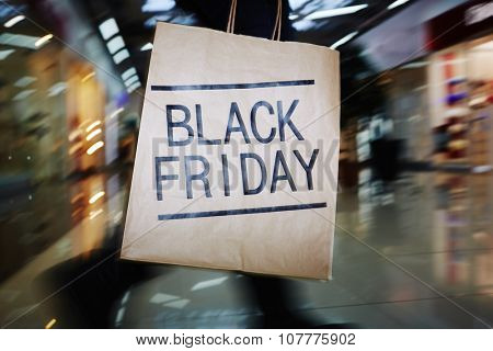 Shopaholic with Black Friday paperbag moving in the mall