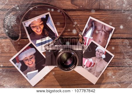 Pretty brunette in santa outfit opening gift against instant photos on wooden floor