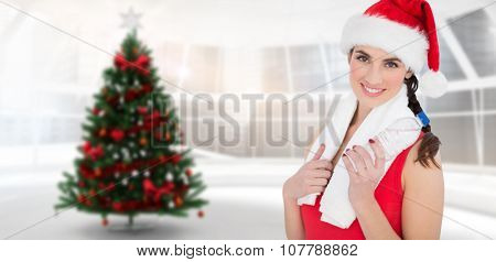 Festive fit brunette smiling at camera against home with christmas tree