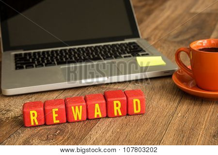 Reward written on a wooden cube in office desk