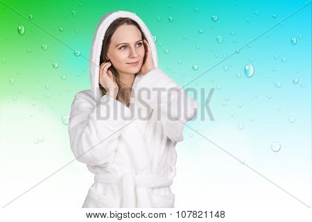 Young woman in white bathrobe stands on the green background poster