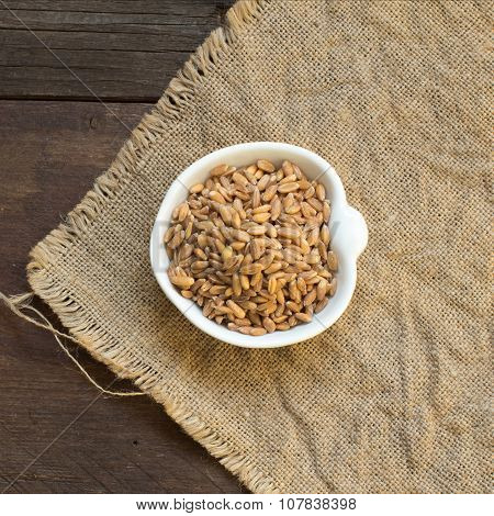 Whole unpolished spelt in a bowl on wood poster