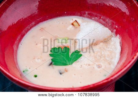 Vegetable potage served in a red cup on a black wooden table