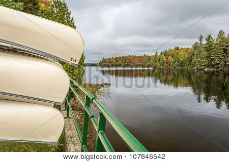 Canoes Stored On A Rack Overlooking A Lake In Autumn