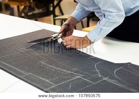 Tailor Working In His Shop Cutting Fabric