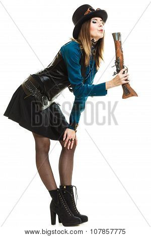Young steampunk islolated girl on white holding and blowing up fancy rifle making interesting pose. Fantasy old fashion with hat goggle. poster