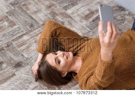 Beautiful attractive charming smiling girl lying on wooden floor in brown sweater and making selfie