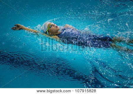 young charming girl swims backstroke
