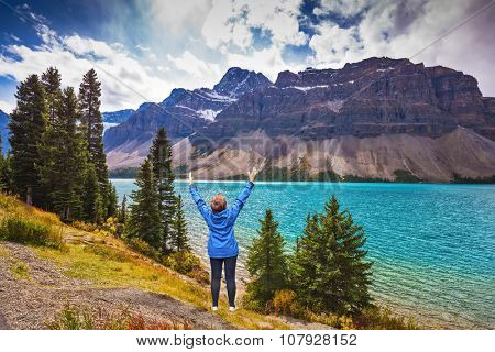 Middle-aged woman in blue jacket in awe of the beautiful nature threw up her hands. The azure waters of lake surrounded by Rocky Mountains and lush autumn yellow and orange vegetation