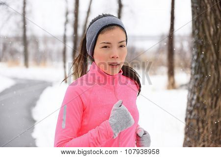 Woman running in cold weather wearing winter accessories, pink windbreaker, gloves and headband. Asian Chinese young adult doing her cardio exercises outside in a city park.