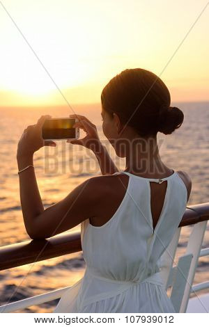Cruise ship vacation woman taking photo with smart phone camera enjoying sunset on travel at sea. Girl using smartphone to take picture of ocean sunset. Woman in dress on luxury cruise liner boat.