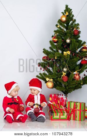 Two children under christmas pine