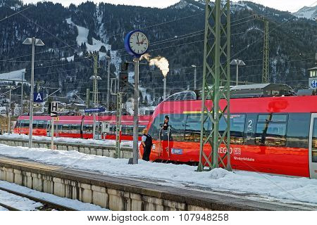 GARMISCH-PARTENKIRCHEN GERMANY - JANUARY 6 2015: Train driver looking out of his cabin at a station stop in Garmisch-Partenkirchen on a sunny winter day.