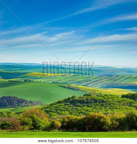 fresh Landscape of fields in countryside - different colors of hills and blue sky, beautiful spring season