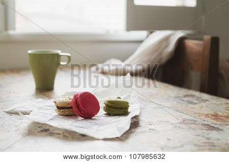 Three Macaroons On Rustic Cafe Table With Coffee Cup